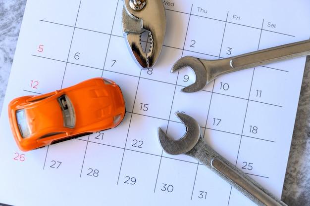 Llave y coche en el calendario con números. concepto de reparación