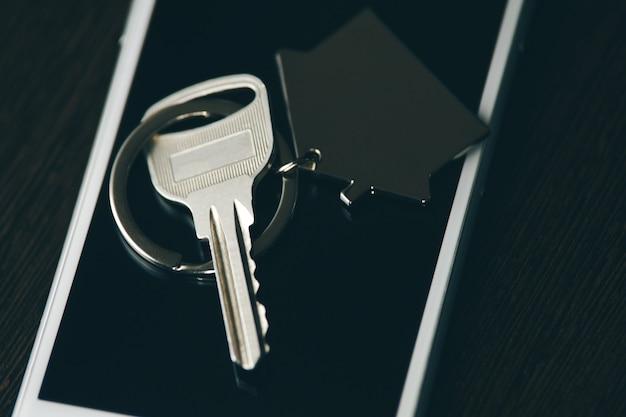 Llave del coche con smartphone aislado sobre fondo oscuro. llave y teléfono