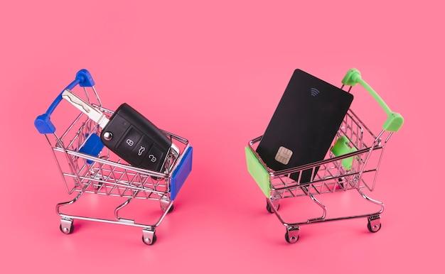 Llave del coche y tarjeta de viaje en la tarjeta de compras azul y verde sobre fondo rosa