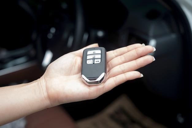 La llave inteligente del coche es un sistema de autorización y acceso electrónico, mano que sostiene la llave inteligente del coche.