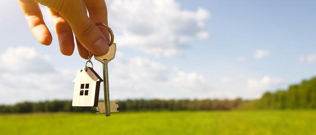Llave y llavero de madera en forma de casa en la mano en un campo