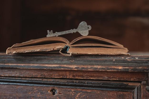 Una llave de madera decorativa descansa sobre un viejo libro vintage abierto Foto Premium