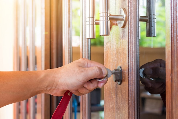 Llave en mano de personas que abren la puerta hacia adentro, la puerta exterior se abre y se pone en la puerta