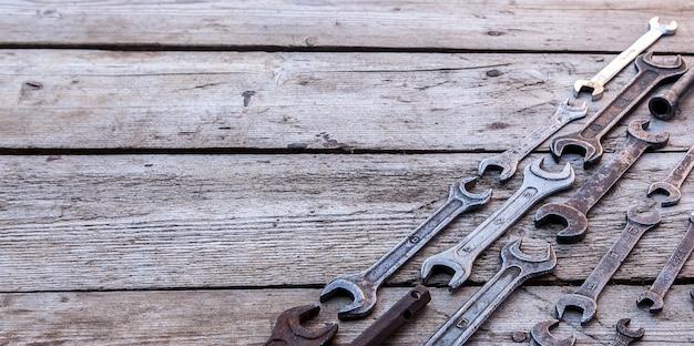 Llave de metal herramientas oxidadas acostado sobre una mesa de madera negra. martillo, cincel, sierra para metales, llave de metal. copie el espacio.