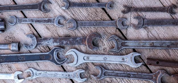 Llave de metal herramientas oxidadas acostado sobre una mesa de madera negra. martillo, cincel, sierra para metales, llave de metal. juego sucio de herramientas de mano sobre un fondo vintage de panel de madera con herramientas.