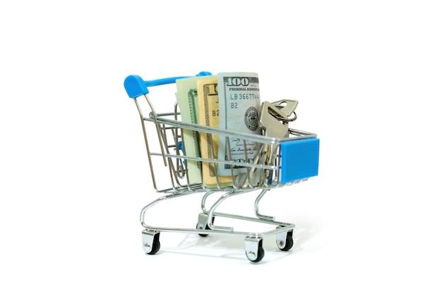 Llave de un nuevo piso y dólares estadounidenses en un pequeño carrito de compras diminuto aislado en un fondo blanco. compra de apartamentos. costoso. comprar. costo. dinero. bienes raíces. mercado. alquiler. ganar