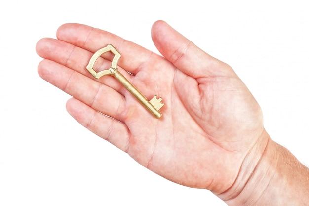 Llave de oro en la palma del símbolo de riqueza de un hombre. en una pared blanca