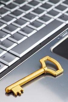 Llave de oro en un símbolo de seguridad portátil en internet. de cerca.