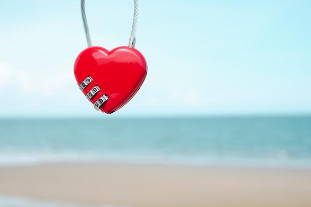Llave roja de la forma del corazón con la playa y el mar del verano. concepto de san valentín.
