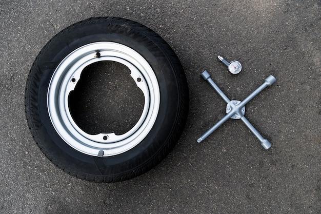 Llave de rueda de coche, rueda y manómetro. reparación de autos