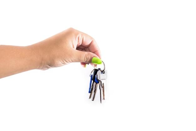 Llaves de apartamento en mano femenina en blanco