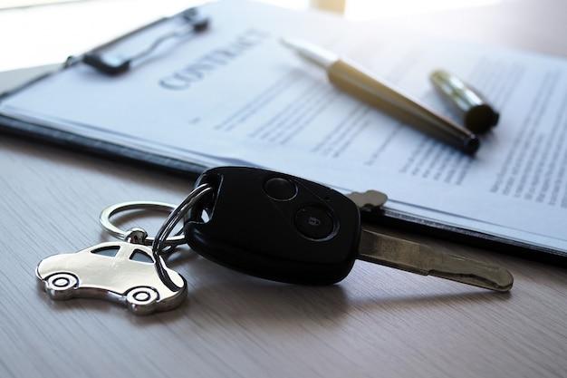 Llaves de automóviles colocadas en documentos contractuales sobre préstamos para automóviles