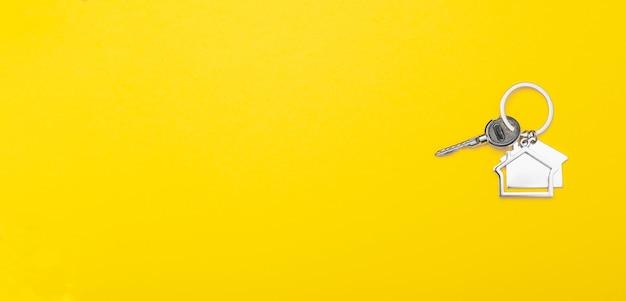 Llaves de la casa con baratija sobre fondo amarillo con lugar para el texto.