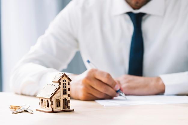 Llaves y casa cerca de escribir agente de bienes raíces