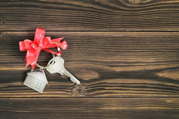 Llaves de la casa con una cinta de moño sobre una encimera de madera