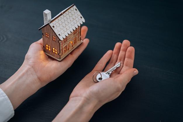 Llaves de la casa en manos de una mujer y una pequeña maqueta de una casa con ventanas luminosas cercanas. concepto de adquirir tu casa