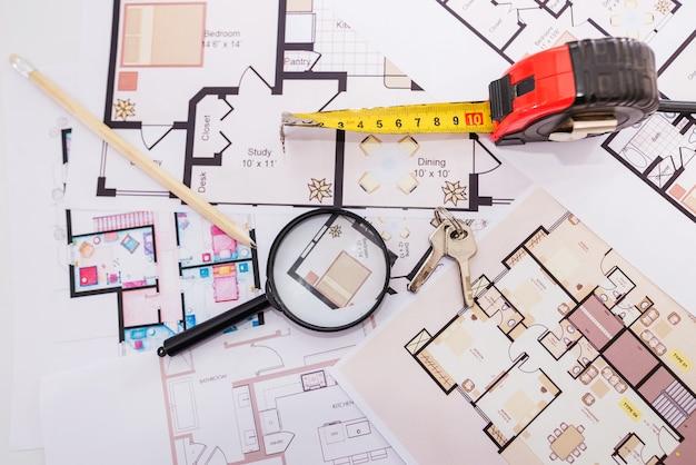 Llaves con cinta métrica y lupa sobre el plano de la casa.