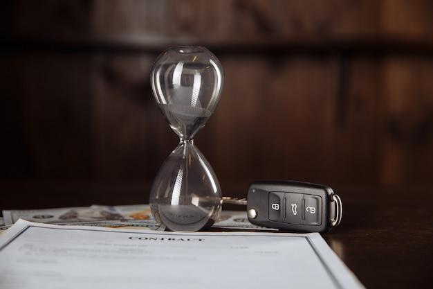 Llaves del coche y reloj de arena en el documento de contrato firmado.