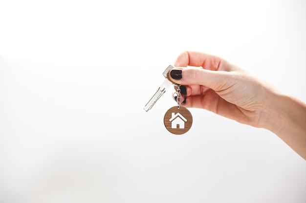 Llaves de concepto de bienes raíces con un llavero con forma de casa en la mano de una mujer