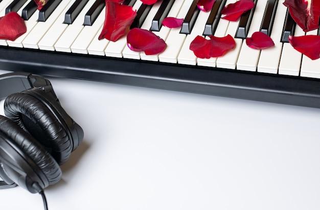 Las llaves del piano derramadas con los pétalos color de rosa rojos y los auriculares, aislados, copian el espacio.
