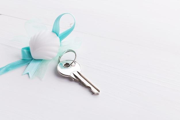Llaves de plata con cinta azul y concha
