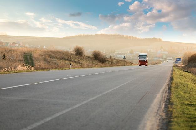 Llegando camión blanco en la carretera en un paisaje rural al atardecer