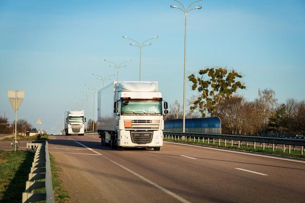 Llegando camión rojo en la carretera en un paisaje rural al atardecer