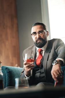 Llegando tarde. abogado de pelo oscuro maduro barbudo mirando su reloj de mano mientras llega tarde