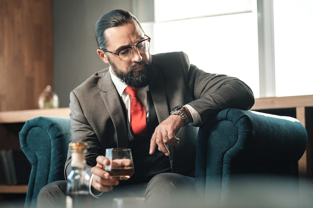 Llegando tarde. hombre de negocios de pelo oscuro próspero barbudo mirando su reloj de mano llegando tarde