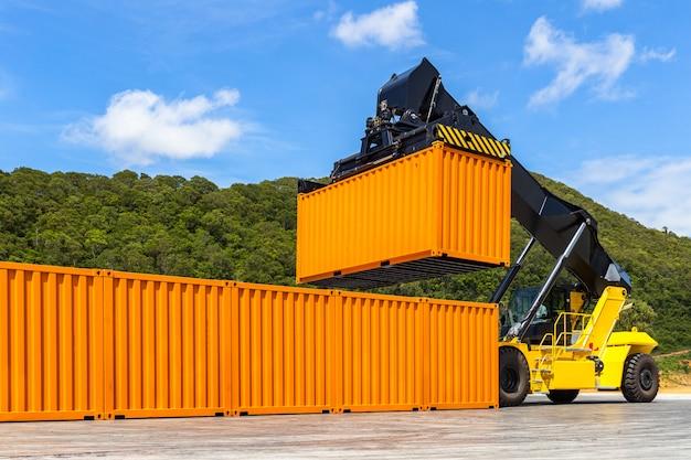 Llegar a la carretilla elevadora amarilla apiladora manejo de contenedores de envío en la importación comercial
