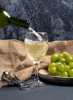 Llenar copa de vino blanco con uvas en ambiente de bodega