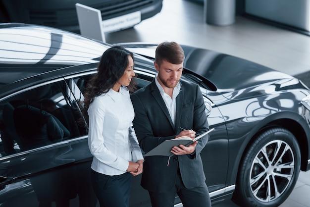 Llenar los documentos. clienta y empresario barbudo con estilo moderno en el salón del automóvil