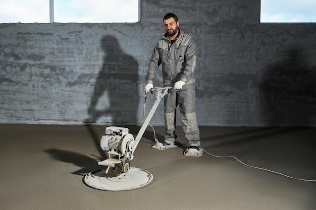 Llenar el piso con concreto, enrasar y nivelar el piso por parte de los trabajadores de la construcción. pavimentos lisos de mezcla de cemento, hormigonado industrial