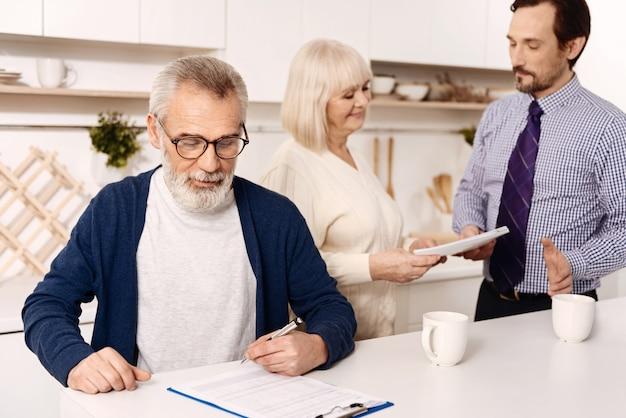 Lleno de confianza . hombre mayor barbudo seguro sentado y firmando contrato mientras su esposa saluda al notario