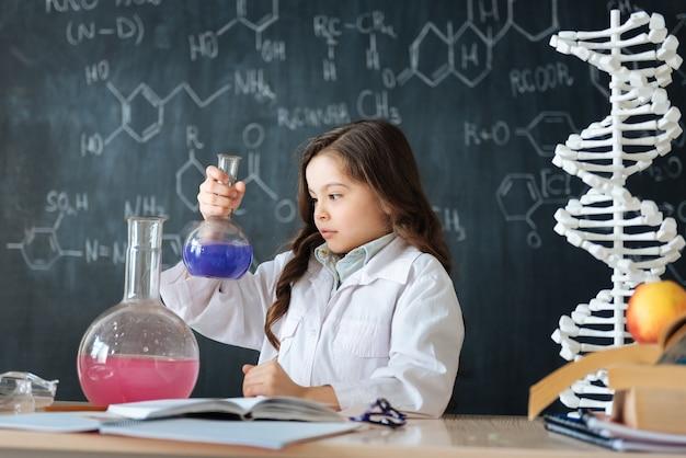 Lleno de determinación. un alumno inteligente y astuto involucrado sentado en el laboratorio y disfrutando de la clase de química mientras participa en el experimento de microbiología
