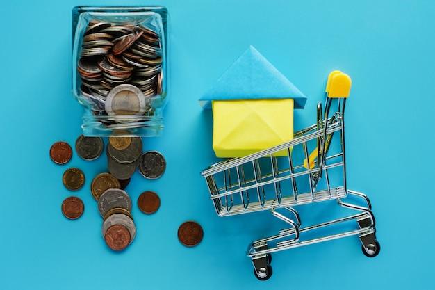 Lleno de dinero y monedas en el frasco de vidrio con carro de compras y modelo de casa
