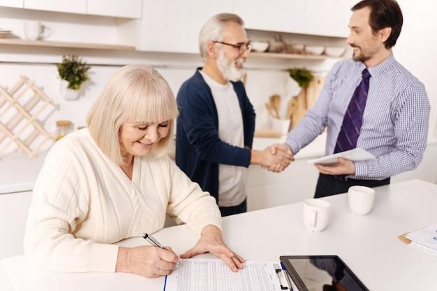 Lleno de felicidad . feliz mujer senior encantadora sentada y firmando contrato mientras su marido saluda al notario