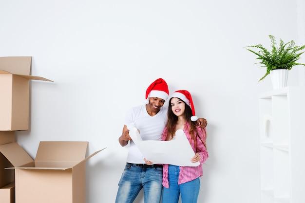 Lleno en movimiento. dos personas con gorro de papá noel en navidad en la casa nueva