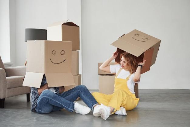 Llevando cajas en las cabezas. pareja feliz juntos en su nueva casa. concepción de mudanza