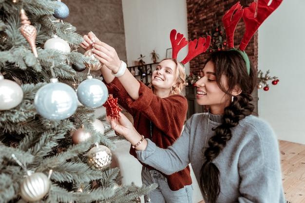 Llevando orejas de ciervo. niñas alegres poniendo juguetes de navidad en el árbol verde en la sala de estar antes de las próximas vacaciones