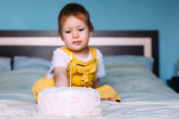 Llittle cute toddler está celebrando su cumpleaños en casa en la cama con pastel