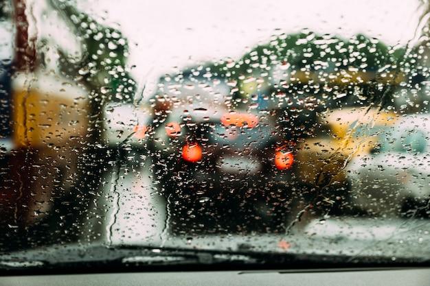 Llueva los descensos sobre el vidrio del coche con el atasco de la falta de definición en el camino en fondo en kolkata, la india.