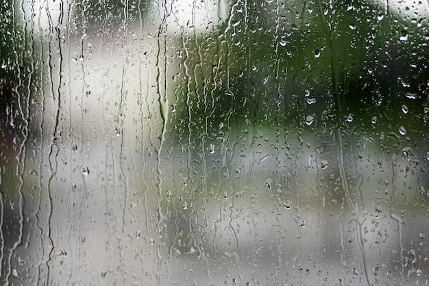 La lluvia cae sobre la ventana con verde