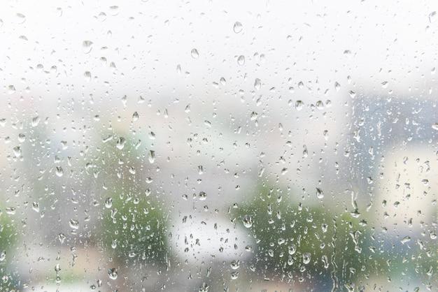 La lluvia cae sobre el vidrio de la ventana con el fondo borroso oscuro.
