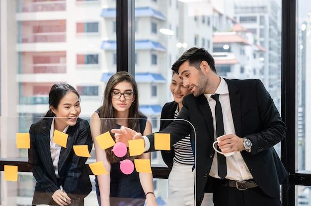 Lluvia de ideas del equipo de negocios multiétnico con discusiones a bordo en la oficina