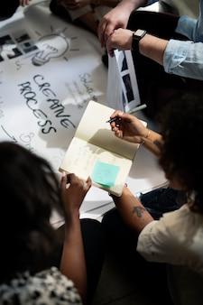 Lluvia de ideas de gente de negocios usando un cuaderno
