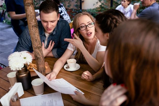 Lluvia de ideas informal de un equipo joven en el acogedor restaurante y pedir comida