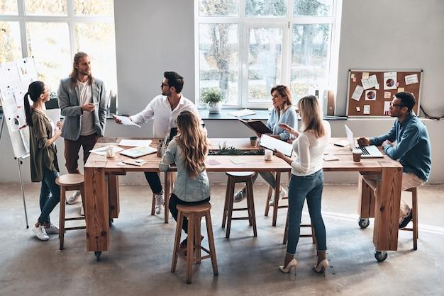 Lluvia de ideas juntos. vista superior de dos colegas jóvenes modernos que realizan una presentación de negocios mientras están de pie en la sala de juntas