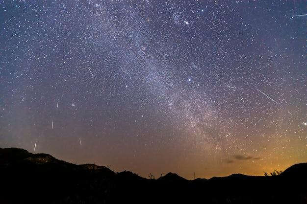 Lluvia de meteoritos gemínida y la vía láctea sobre una montaña. meteorito gemínico en el cielo nocturno