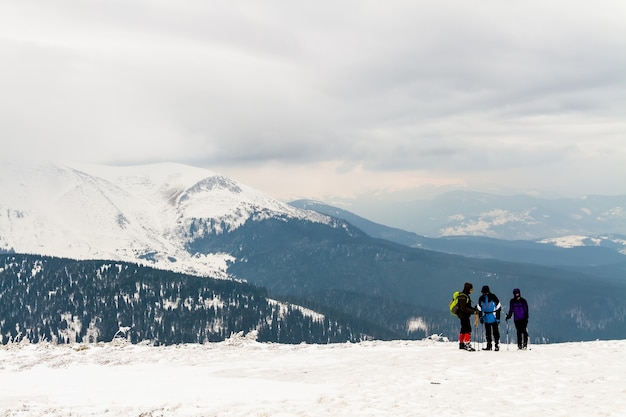 En lo alto de las montañas hay un grupo de tres personas.
